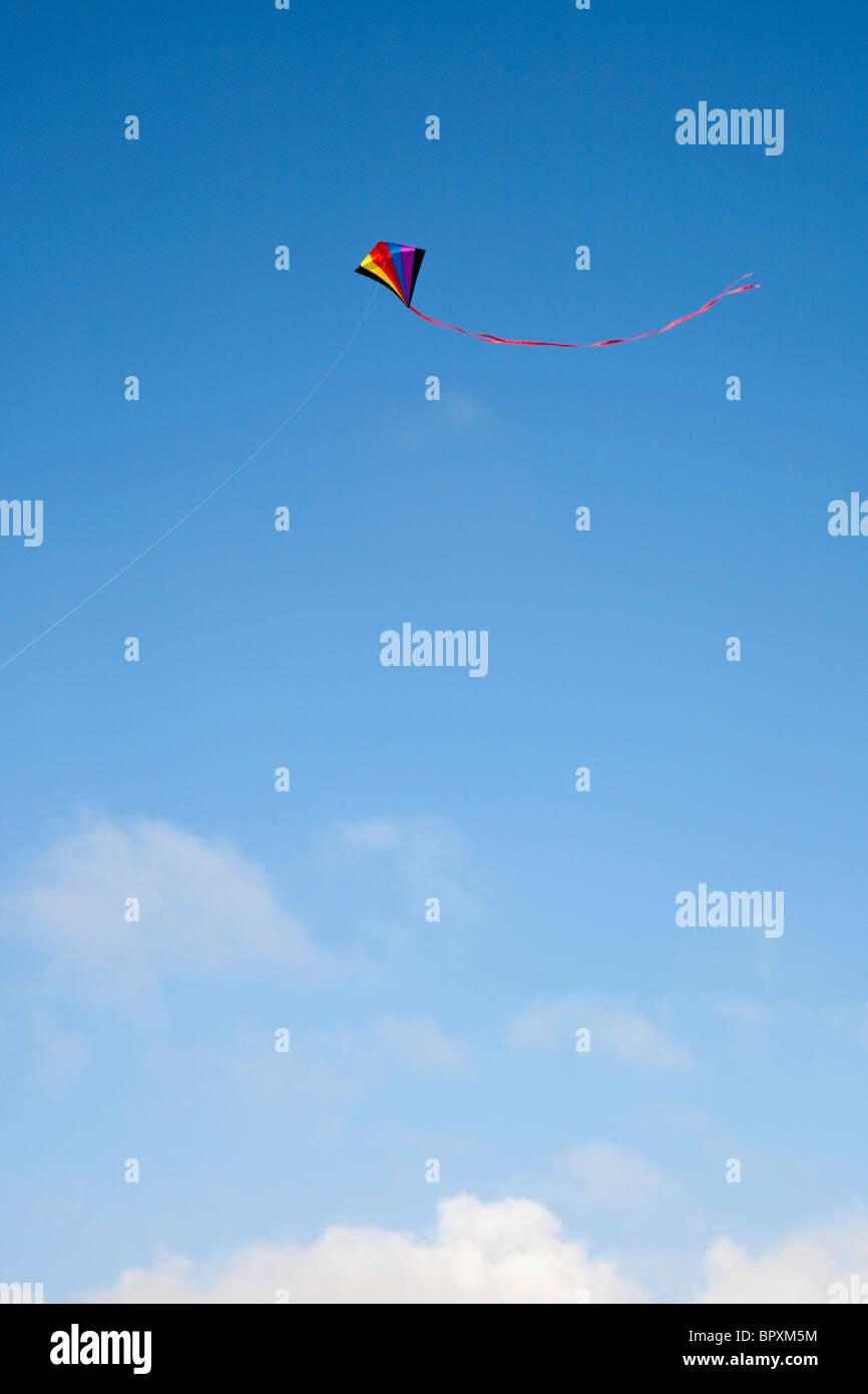 kite flies in blue sky - Stock Image
