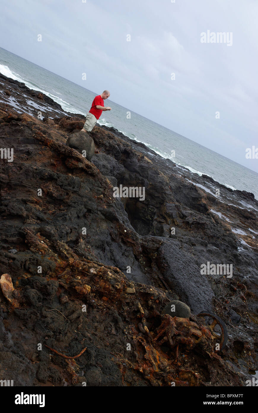 A man stands on the shores of Glass Beach, Hawaii, observing the decomposing trash littering the shores. - Stock Image