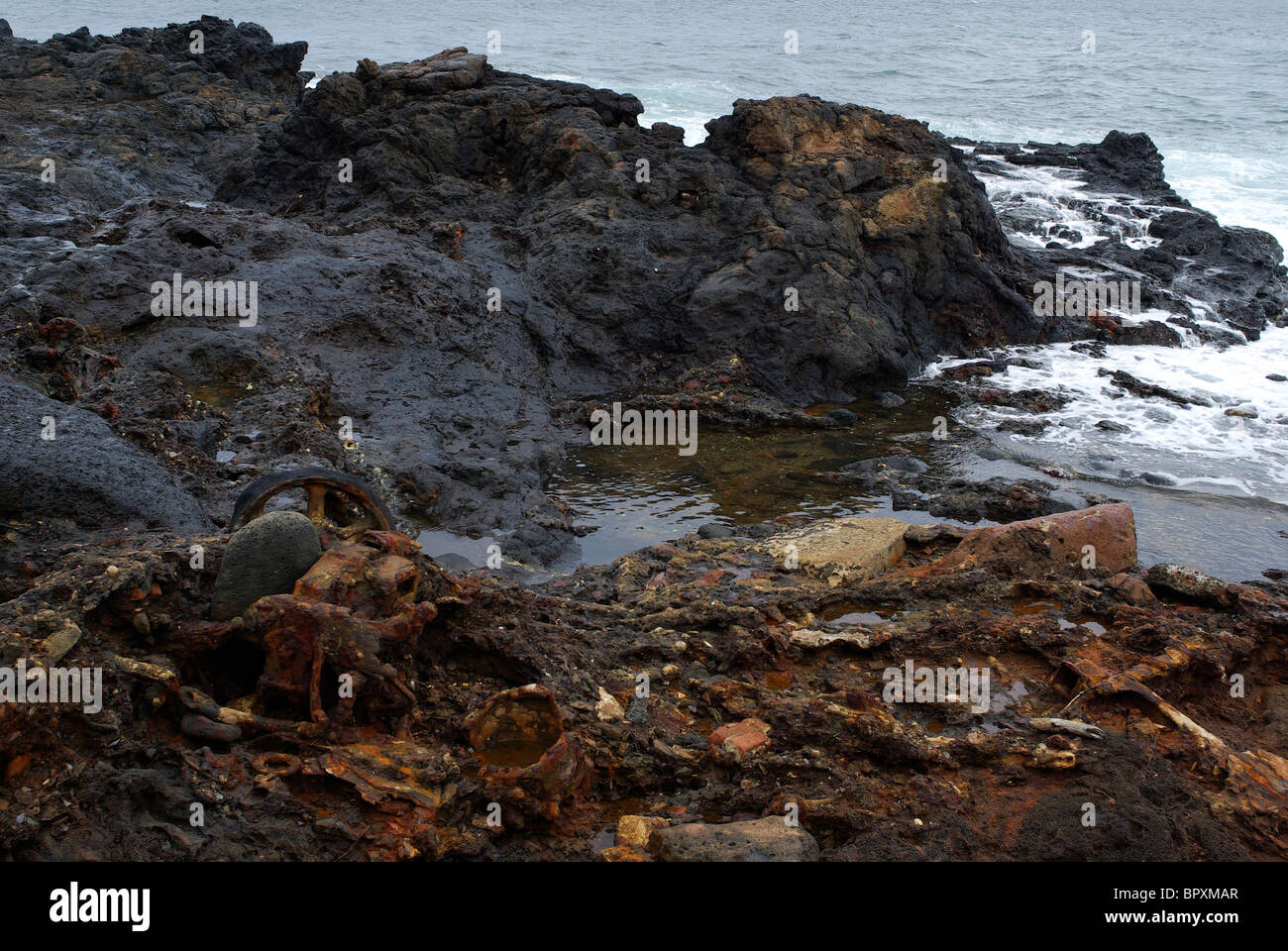 Decomposing trash litters the shore of Glass Beach in Hawaii. Glass Beach was a former garbage dump. - Stock Image