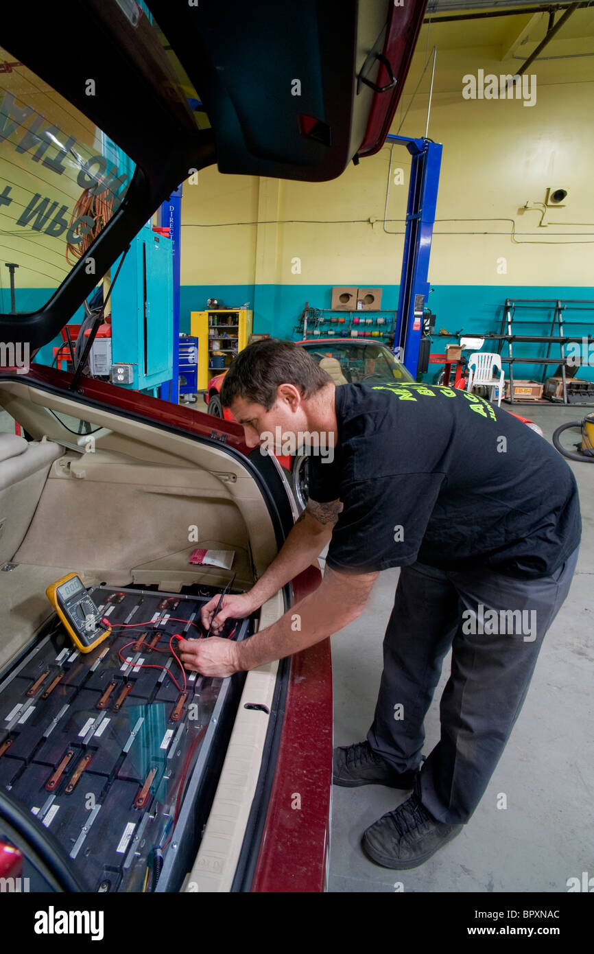 A technician at a California vehicle modification shop checks the voltage of a Toyota Prius hybrid car's main - Stock Image