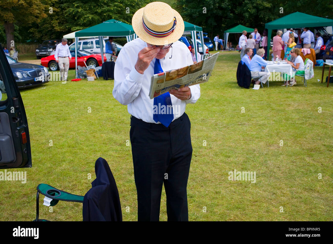 An old man in a straw boater reads the Daily Telegraph newspaper through a pair of glasses. - Stock Image