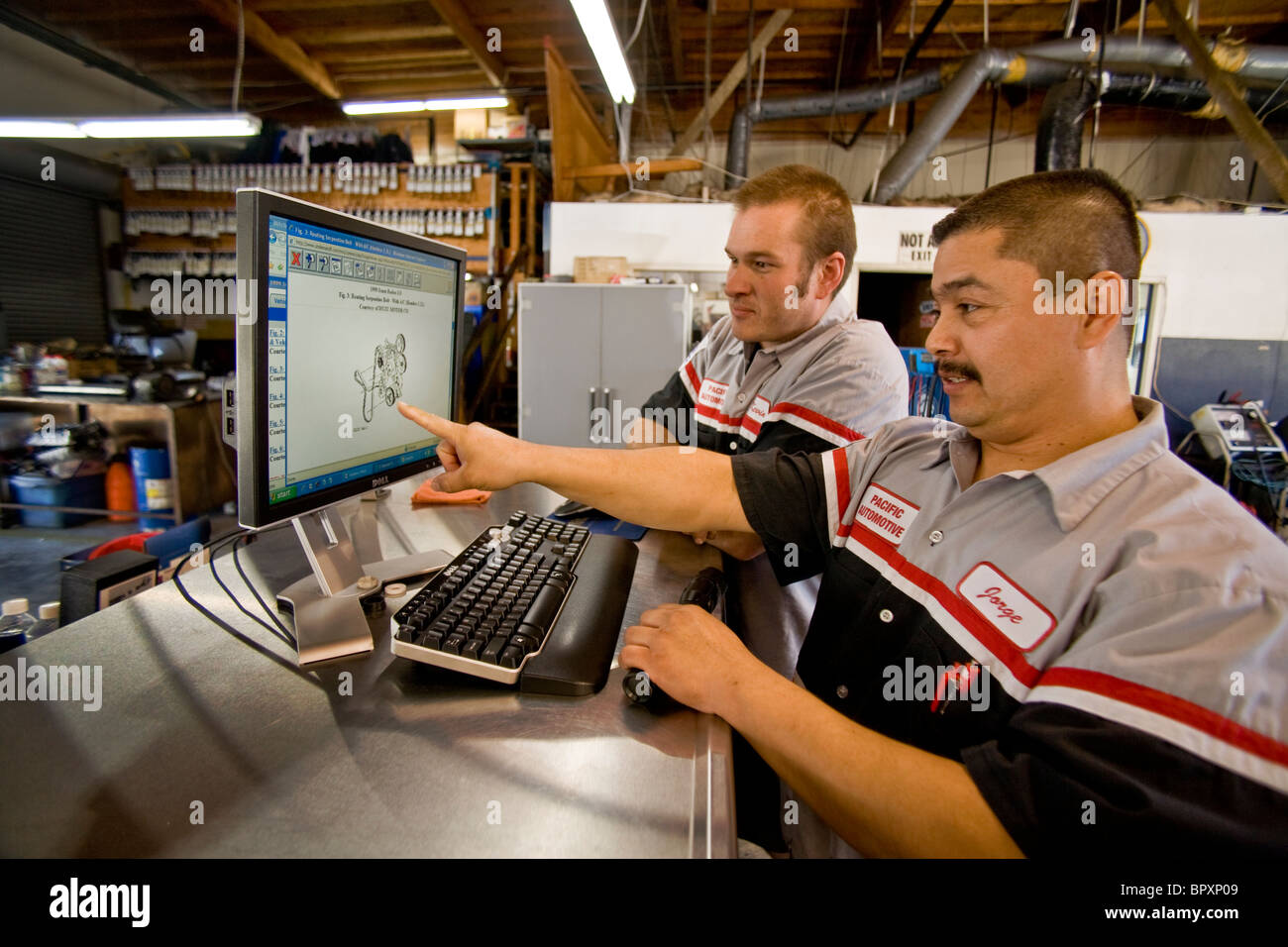 Checking a schematic image of an automobile engine on a computer monitor, two mechanics in an independent Southern - Stock Image
