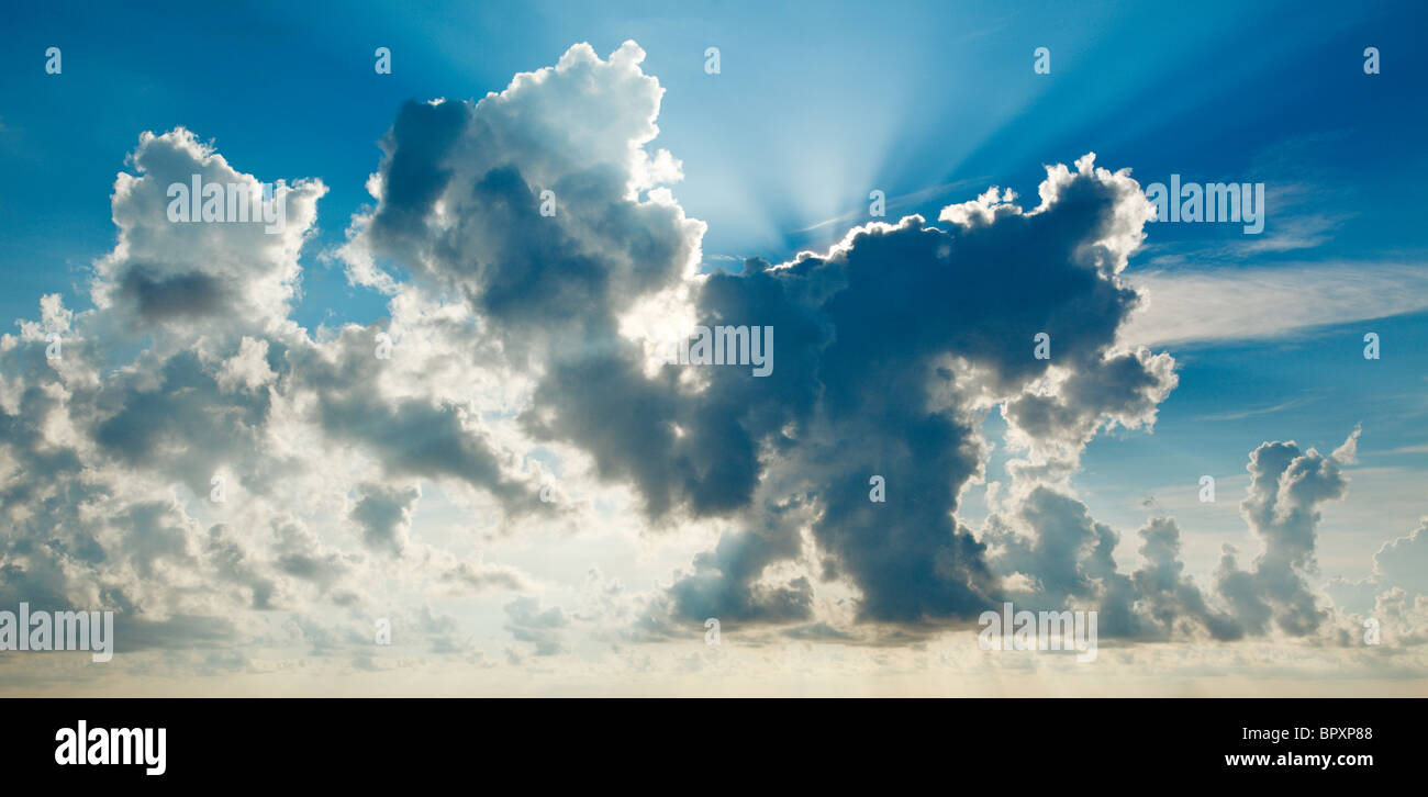 Clouds in sky with sunrays on sunrise - Stock Image