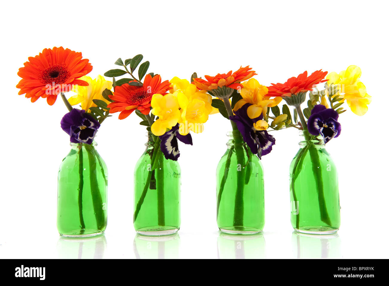 Colorful flower bouquets in green bottles isolated over white Stock ...