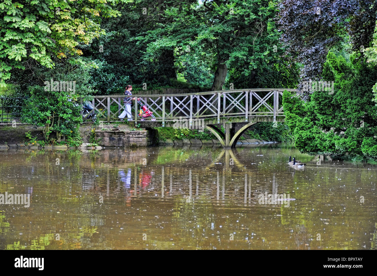 A young mum crossing a  bridge in Birkenhead Park - Stock Image