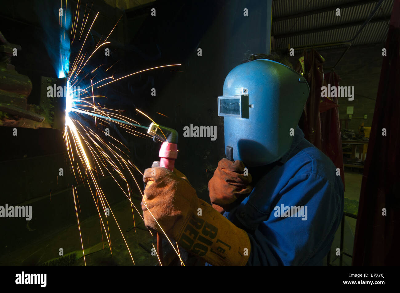 A high school student learning welding skills at a training centre - Stock Image