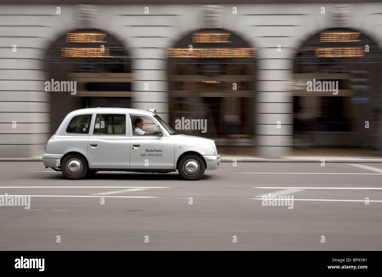 Taxi passing The Ritz Hotel, London - Stock Image