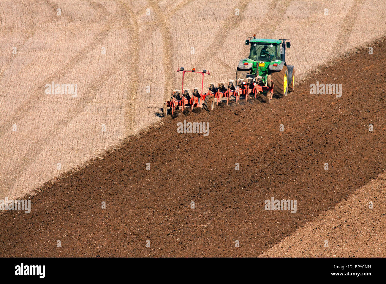 A tractor and plough ploughing a field - Stock Image