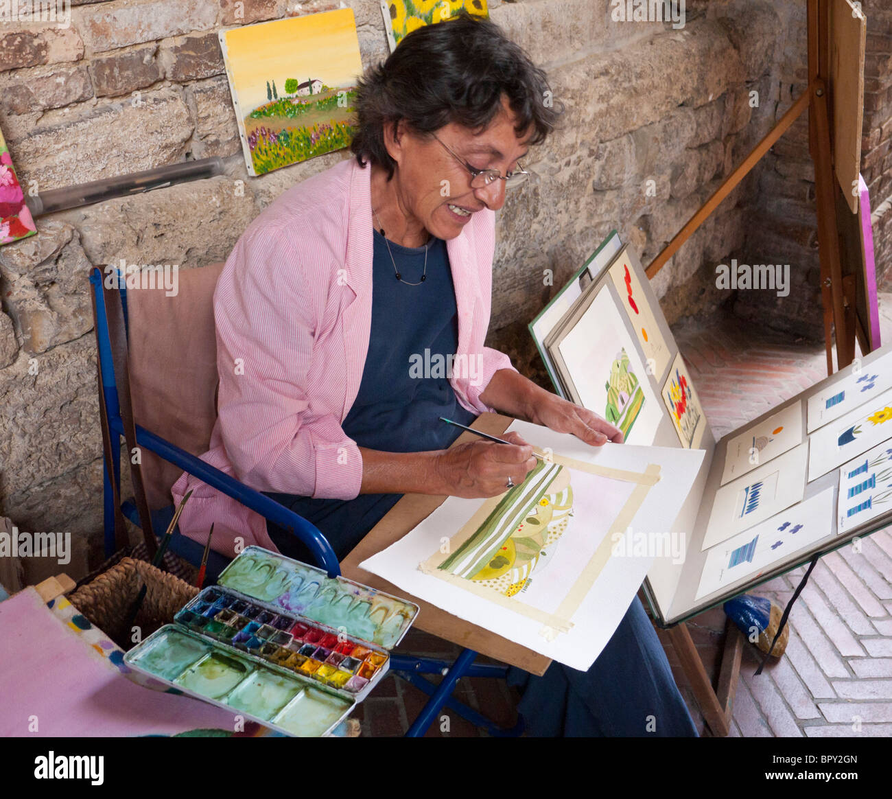 Sitting in front of ancient walls in San Gimignano, painter Anna Ragone paints watercolors - Stock Image