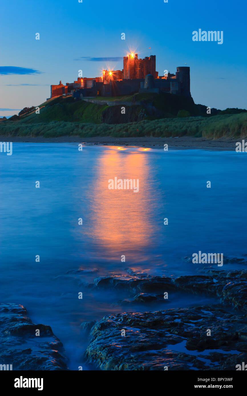 Bamburgh Castle at sunrise on the east coast of Northumberland, England. - Stock Image