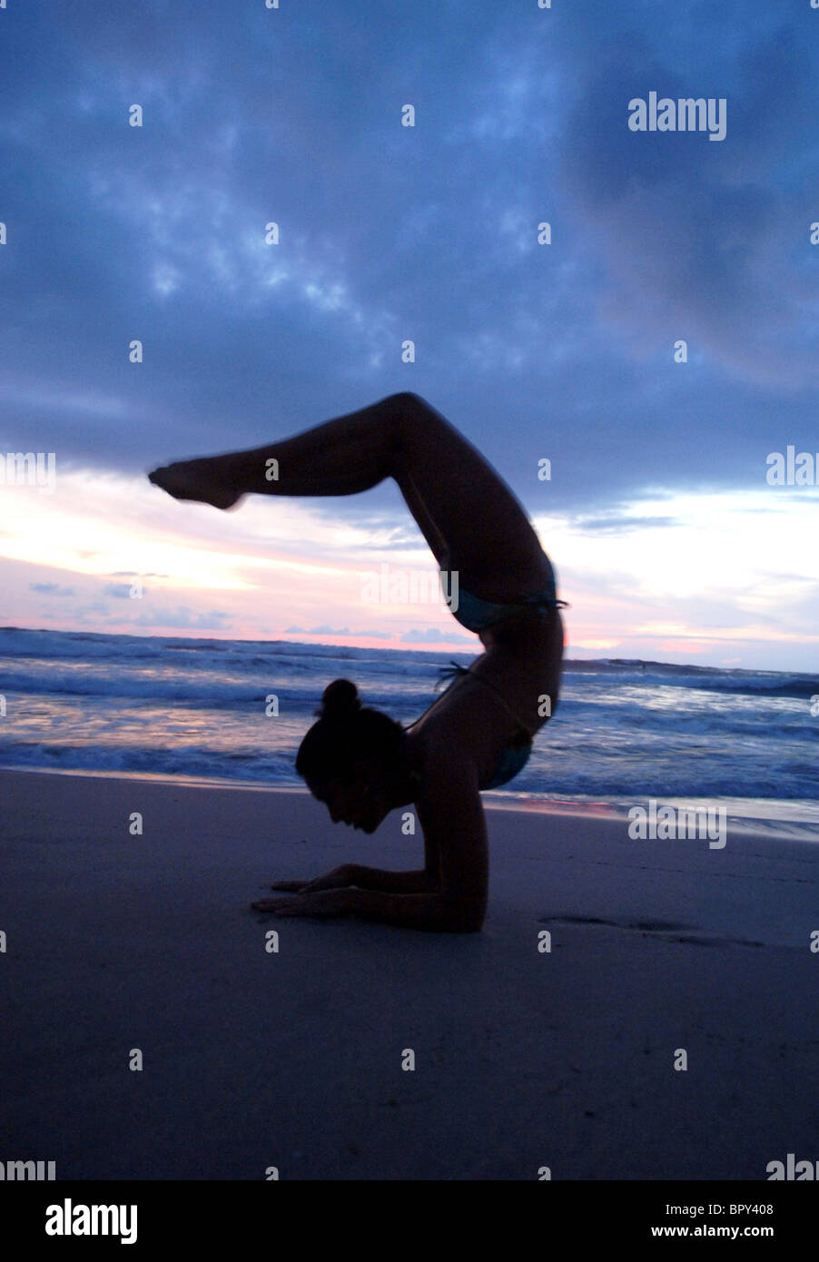 Female performs yoga on beach near water - Stock Image