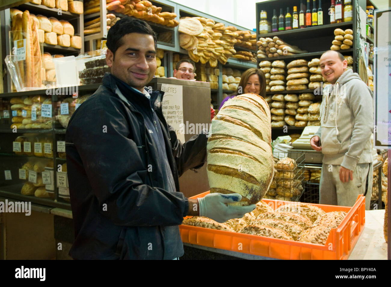 Man delivering crusty bread from a bakery in the early morning to  retail outlet, Queen Victoria Market in Melbourne, - Stock Image
