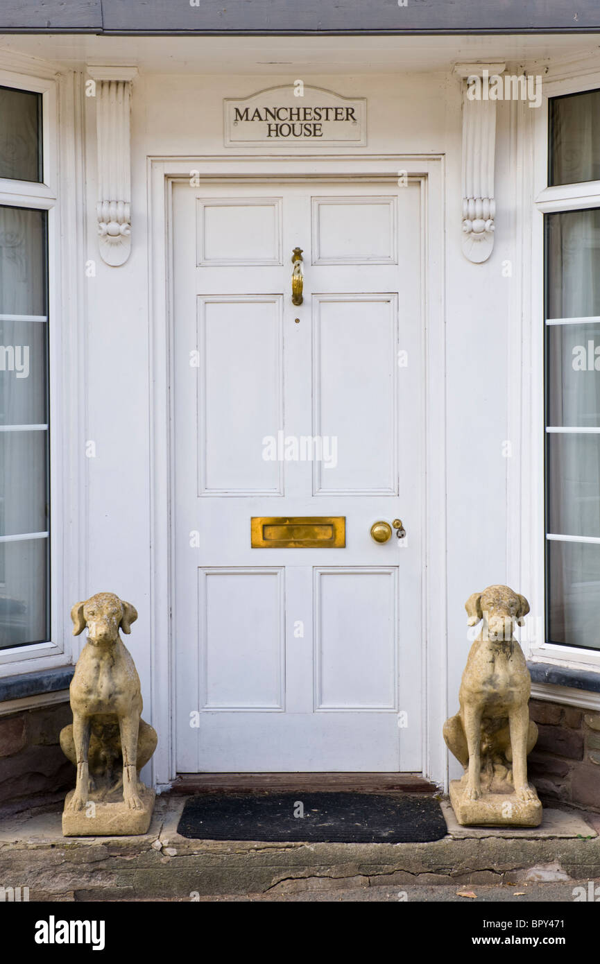 White Painted Wooden Paneled Front Door Of House With Brass Letterbox  Knocker Knob And Stone Hound Dogs Sitting Outside