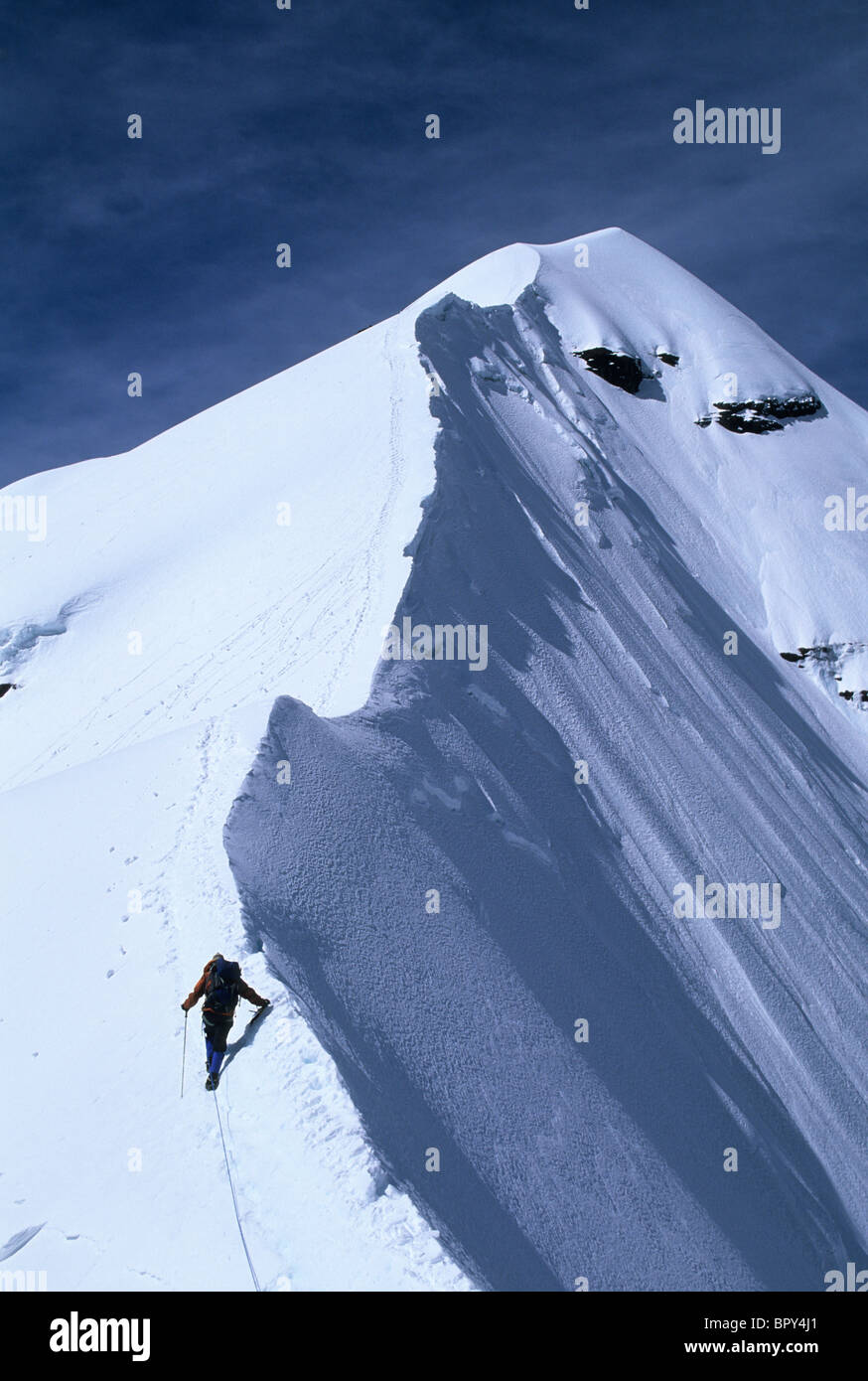 A mountain climber approaches the summit of Pequeno Alpamayo, Cordillera Real, Bolivia - Stock Image