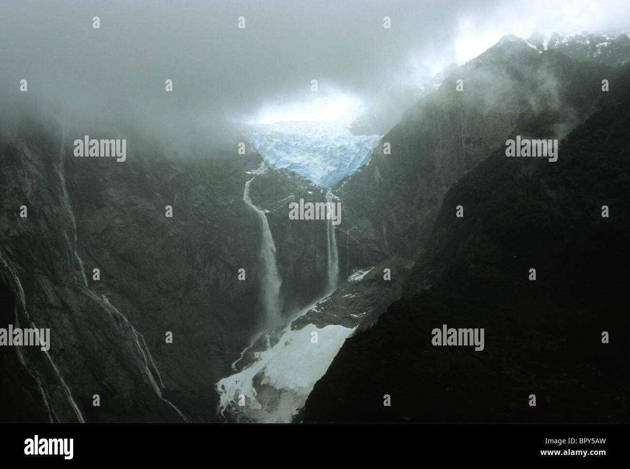 Waterfalls cascade down cliffs from a hanging glacier, Queulat National Park, Southern Chile - Stock Image