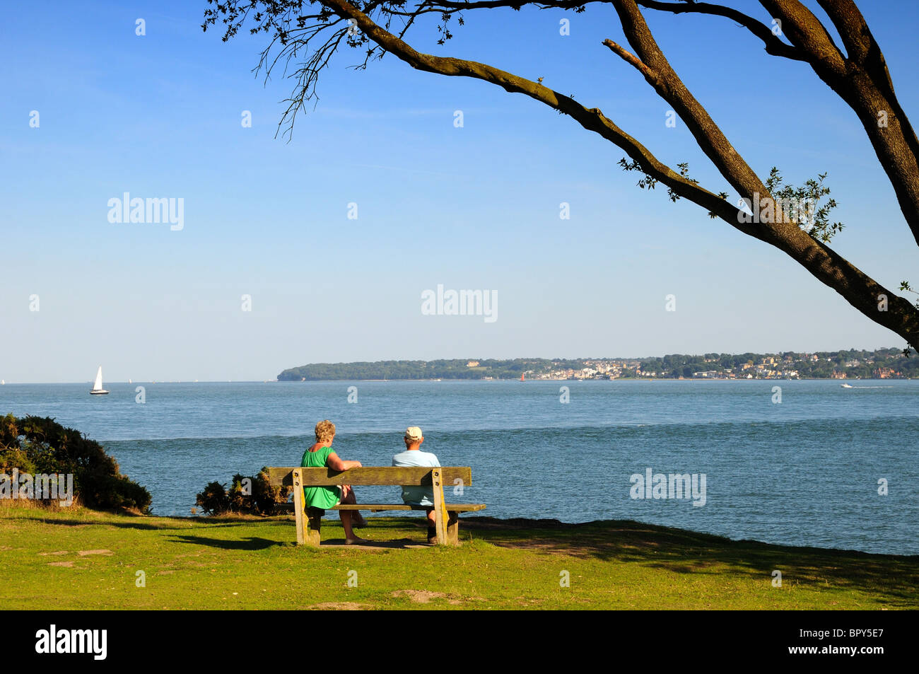 Two people sitting on bench looking at the Solent and the Isle of Wight - Stock Image