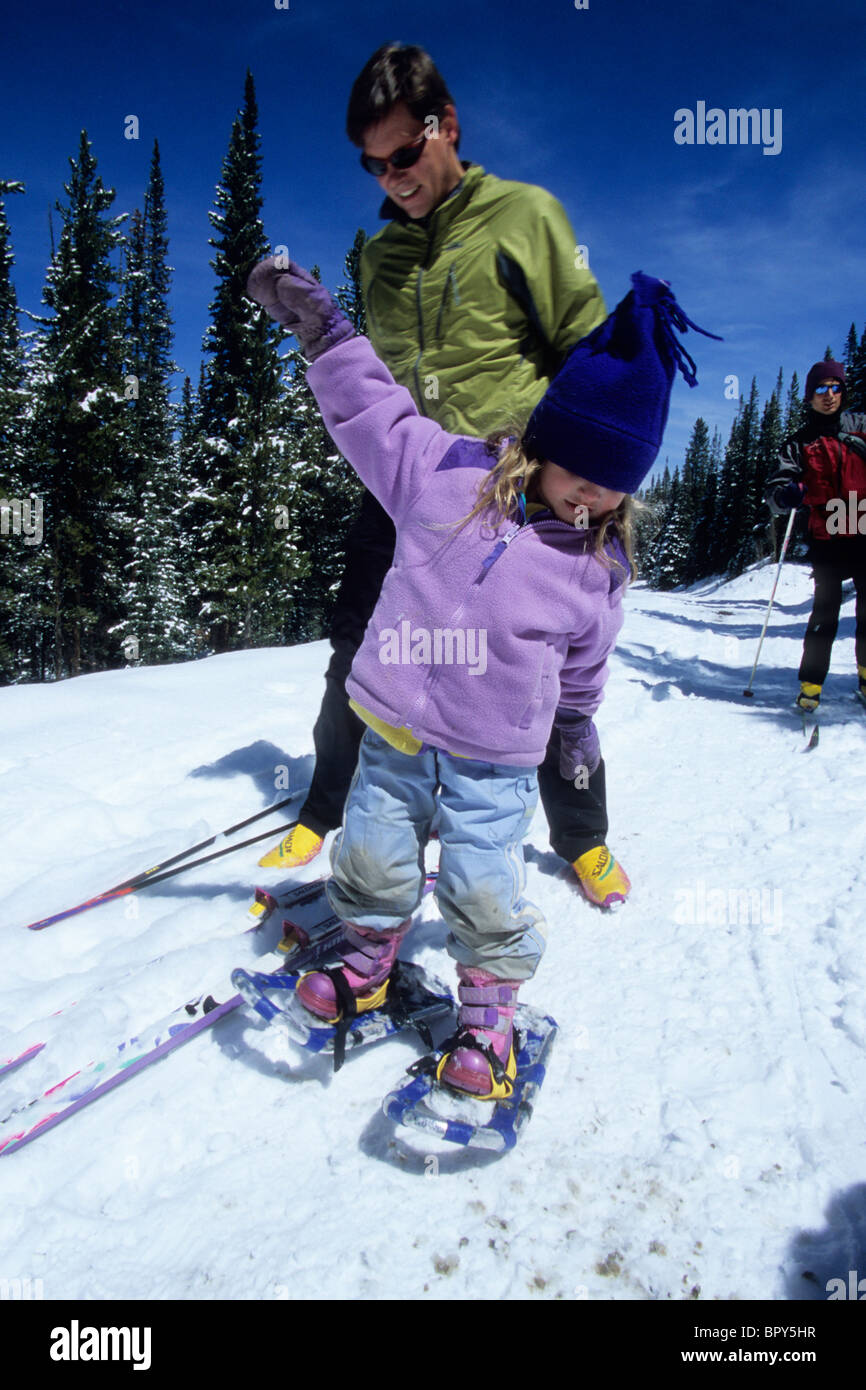 A father helps his daughter snowshoe, on a trail outside Breckenridge, CO Stock Photo