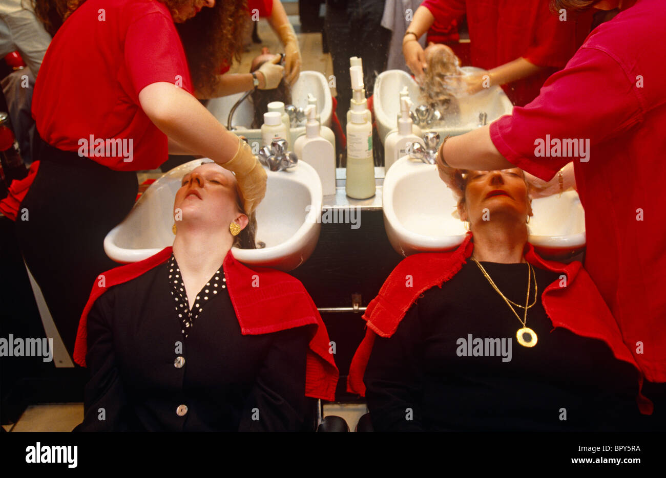 Businesswomen having shampoo sit side-by-side with both their heads tilted back into two sinks in a City of London - Stock Image