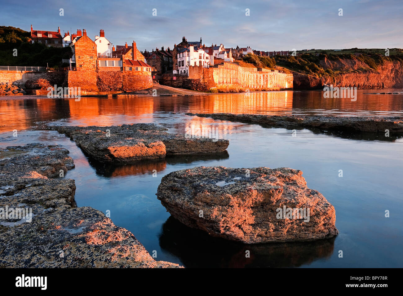 Early morning sun on the rocks and village at Robin Hood's Bay - Stock Image