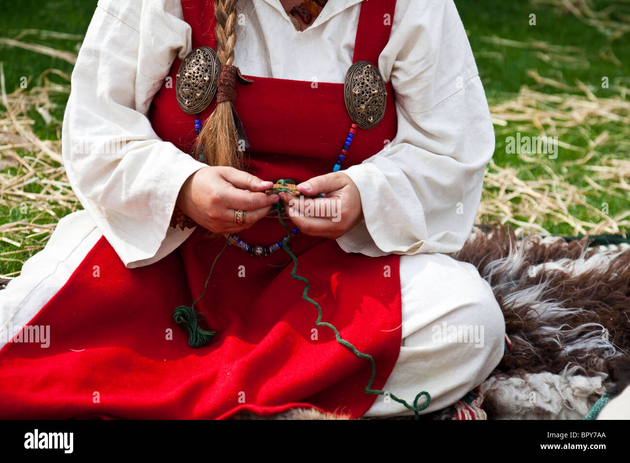 Detail of a woman historical re-enactor wearing Viking clothes (underdress and hangerock) and doing craft work at - Stock Image