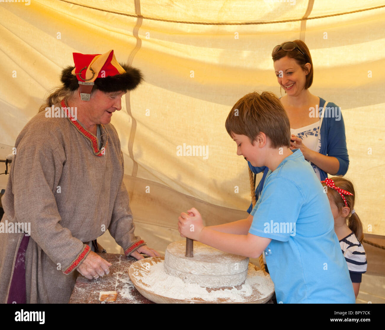 Male Viking re-enactor showing child how to grind corn at the Viking Village of Largs Viking Festival, 2010 - Stock Image