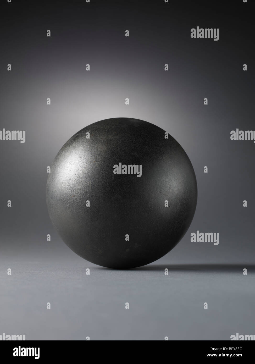 Metal ball with a halo on a grey background - Stock Image