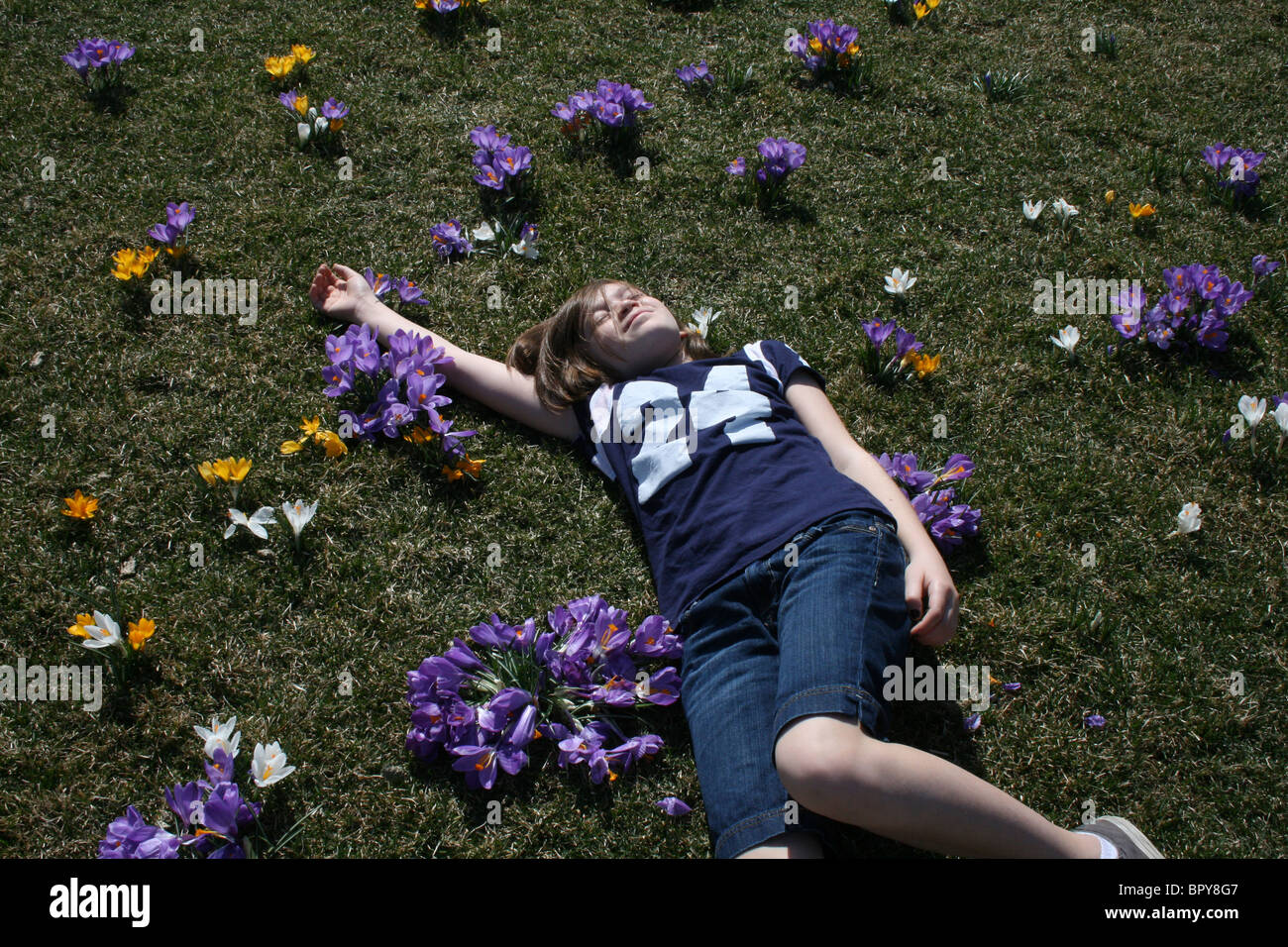 Ahhh youth! A my, a young girl, soaks up the sun with not a care in the world amidst flowers blooming in a meadow. - Stock Image
