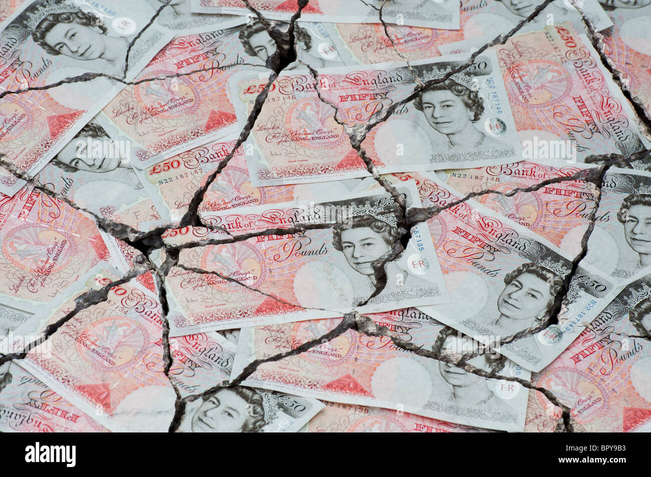 Cracked fifty pound notes concept to represent an economic crisis - Stock Image