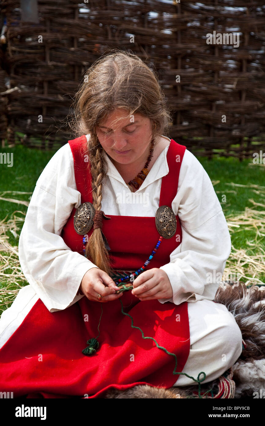 Woman historical re-enactor wearing Viking clothes (underdress and hangerock) and doing craft work at - Stock Image
