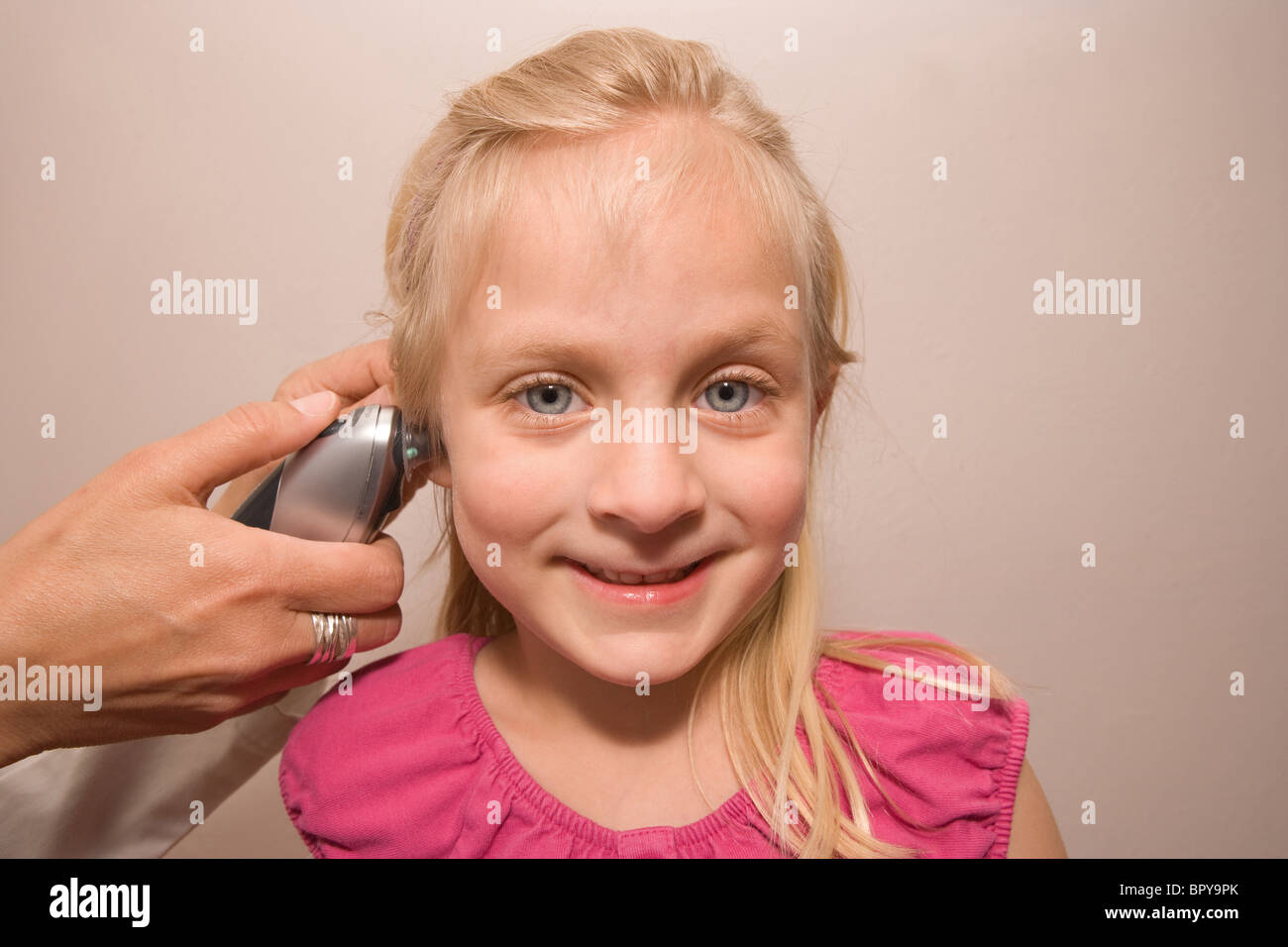 doctor takes temperature of a young girl thermometer in ear electronic wellness checkup fever - Stock Image