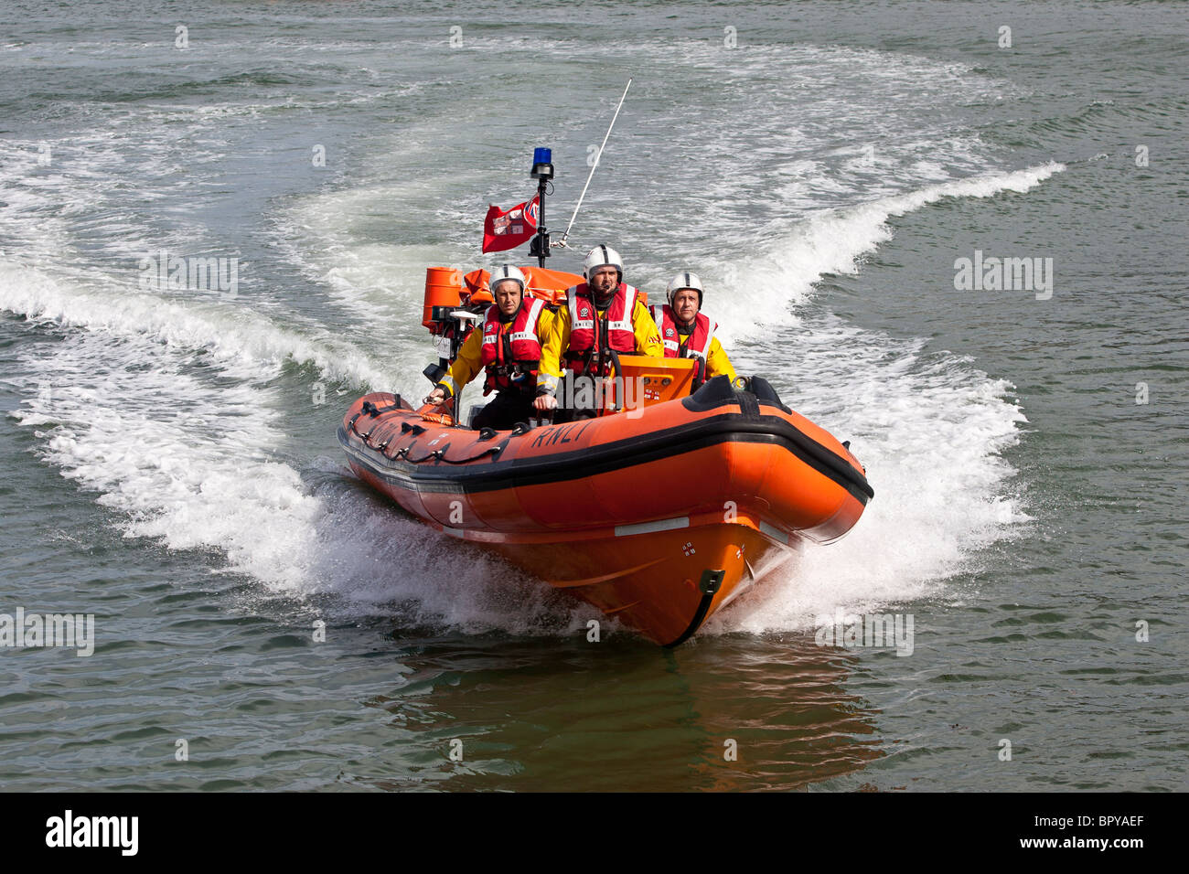 Staithes inshore lifeboat, approaches the harbor, with the sea in the background and three lifeboat men driving Stock Photo
