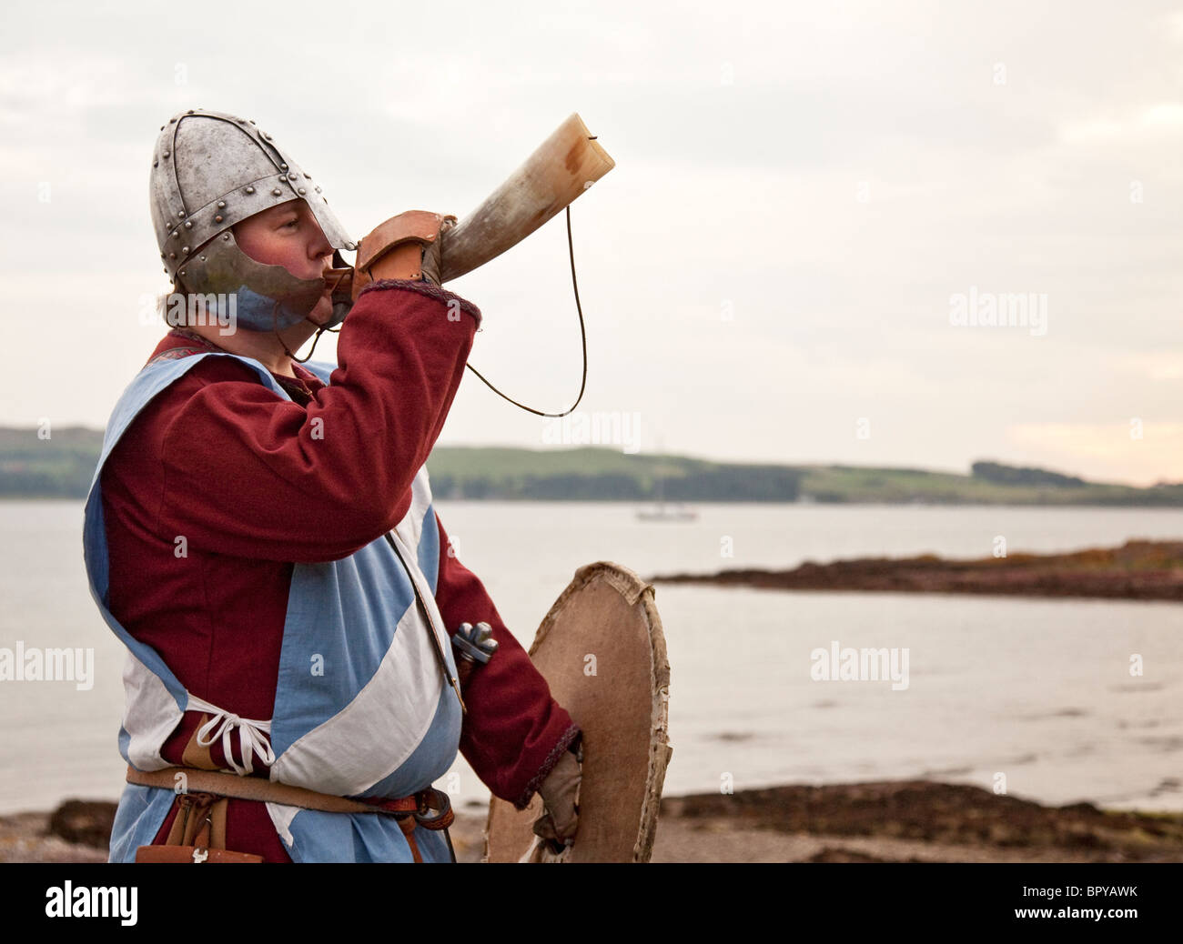 Man dressed as a 13th century Scottish soldier blowing horn preparing to re-enact the Battle of Largs. River Clyde - Stock Image