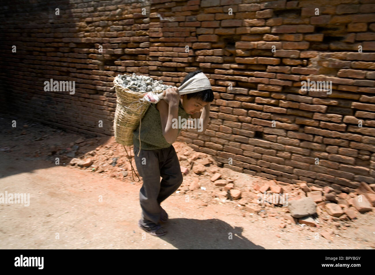 Young boy carrying stones with a basket over his head and shoulder, Bakthapur, Kathmandu, Nepal - Stock Image