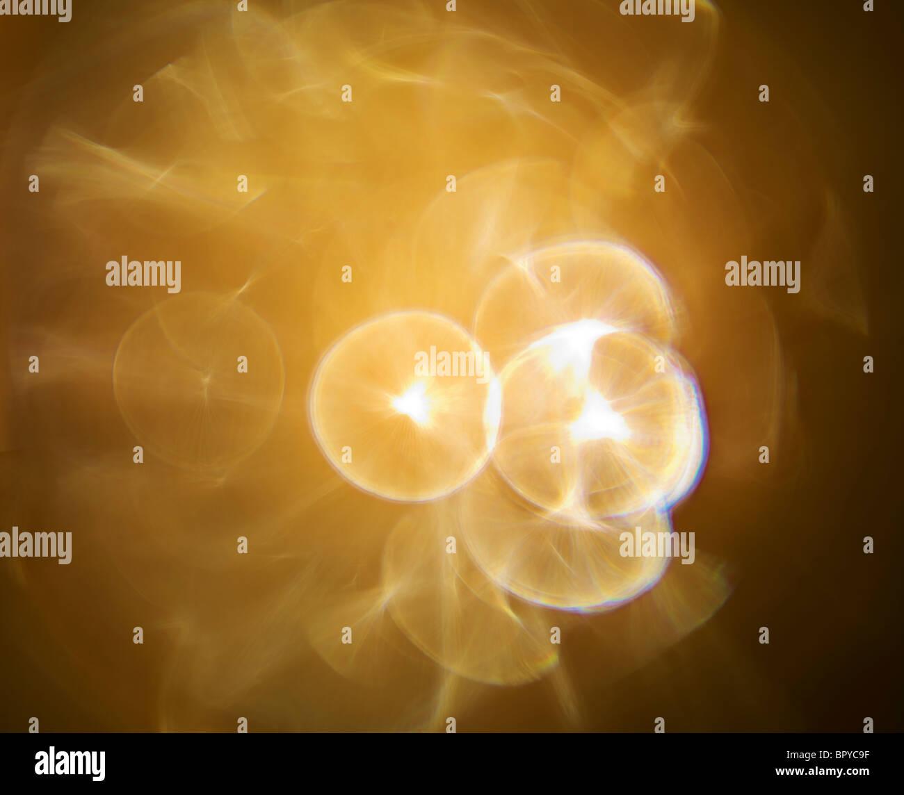Lens flare yellow star burst light that creates the nebulous feel - Stock Image