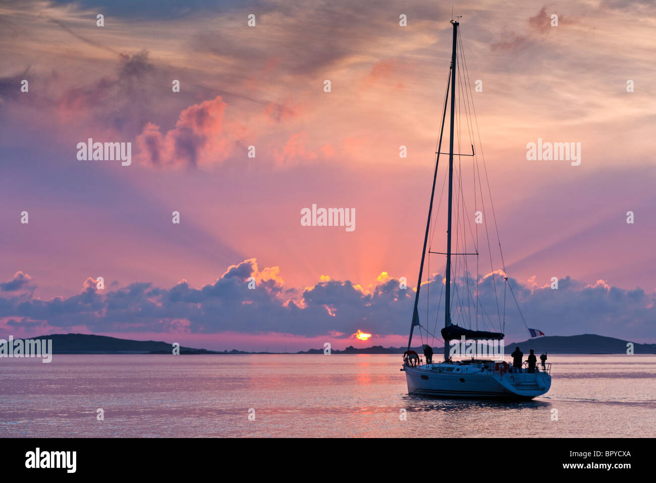 Yacht Silhouette at sunset locking towards Sampson and Tresco Isles of Scilly UK - Stock Image