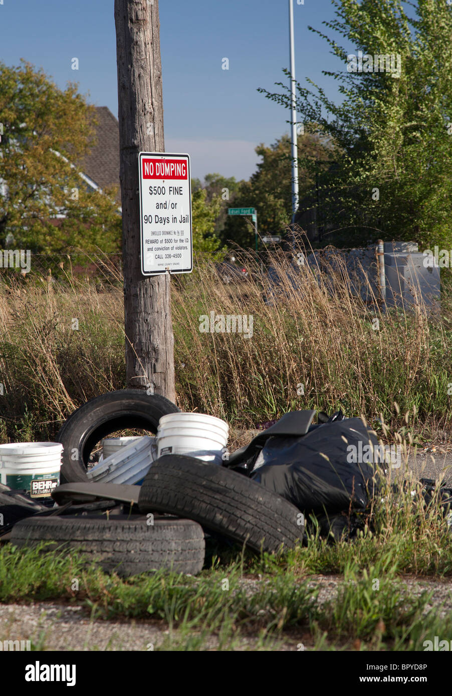 Detroit, Michigan - Old tires and other garbage is dumped in an alley next to a sign warning of penalties for illegal - Stock Image