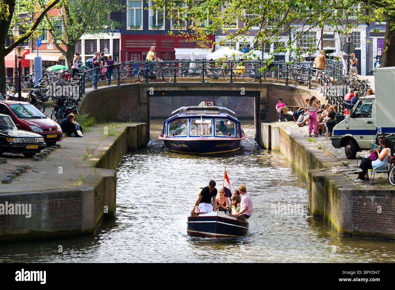 Amsterdam. Canal cruise tour boat and small sloop in the Leliegracht Canal with sidewalk cafes. Tourists sitting - Stock Image