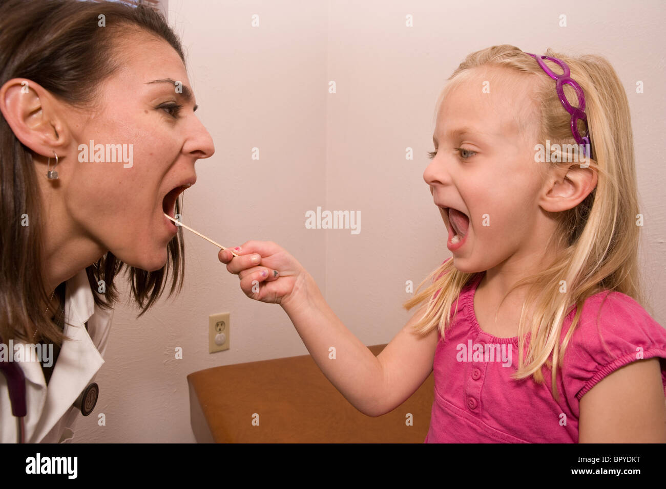 child looks into doctor's mouth with a tongue depressor, reversing roles, looking at tonsil - Stock Image