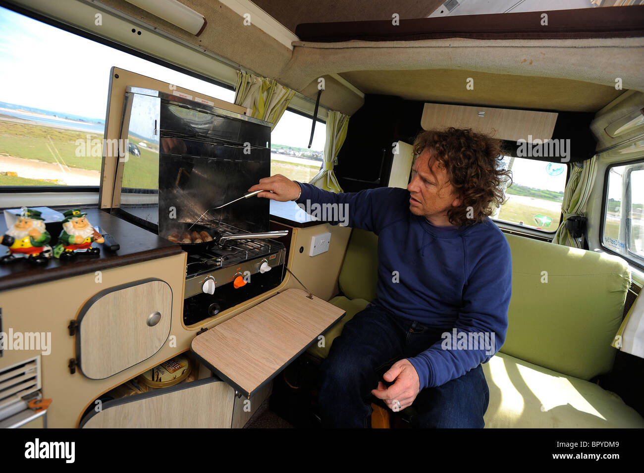 Author and TV presenter Martin Dorey, pictured cooking in his campervan in North Devon - Stock Image