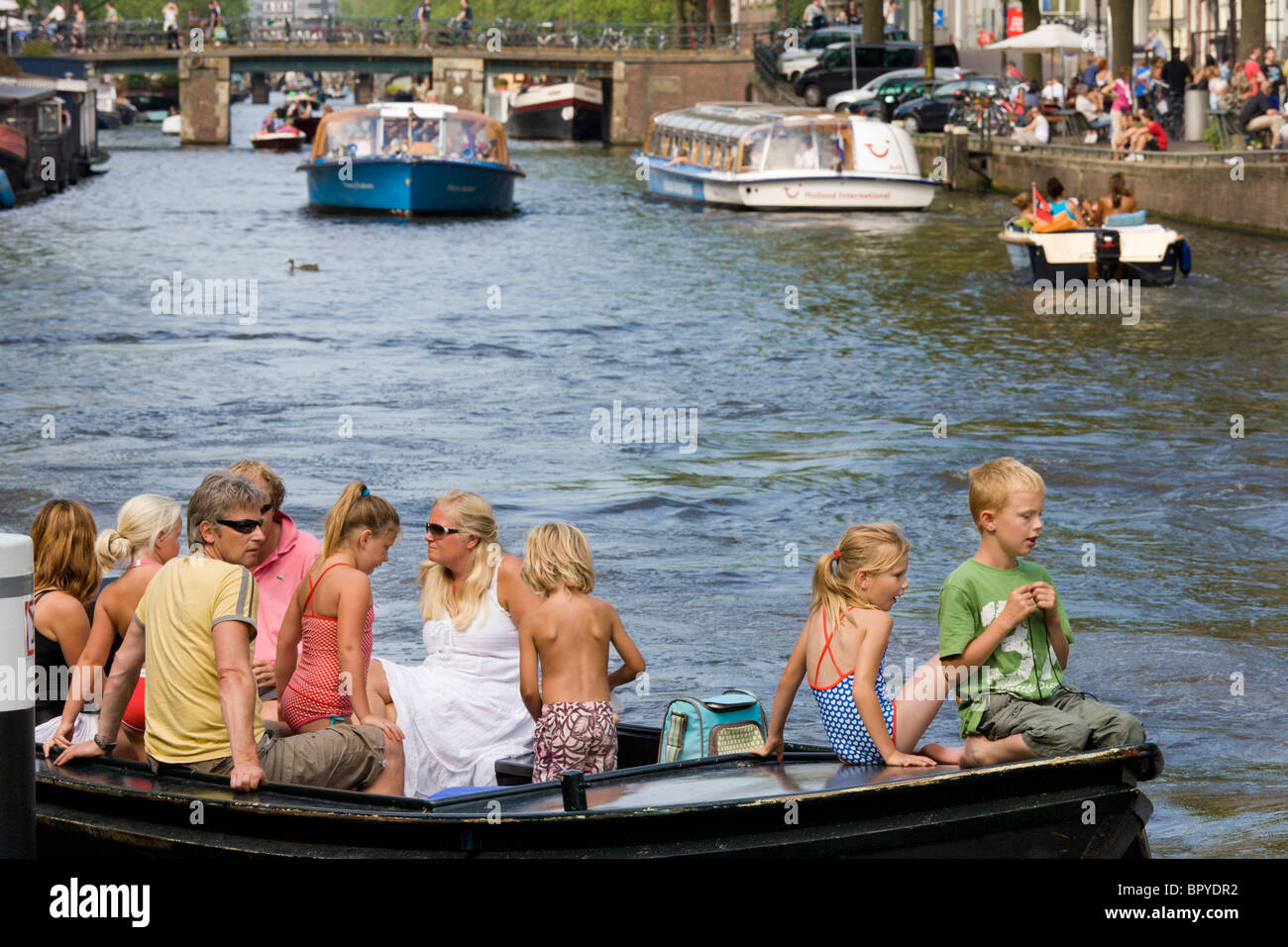 Amsterdam boating. Family with children in small open boat on the Prinsengracht Canal, with canal tour boats in - Stock Image