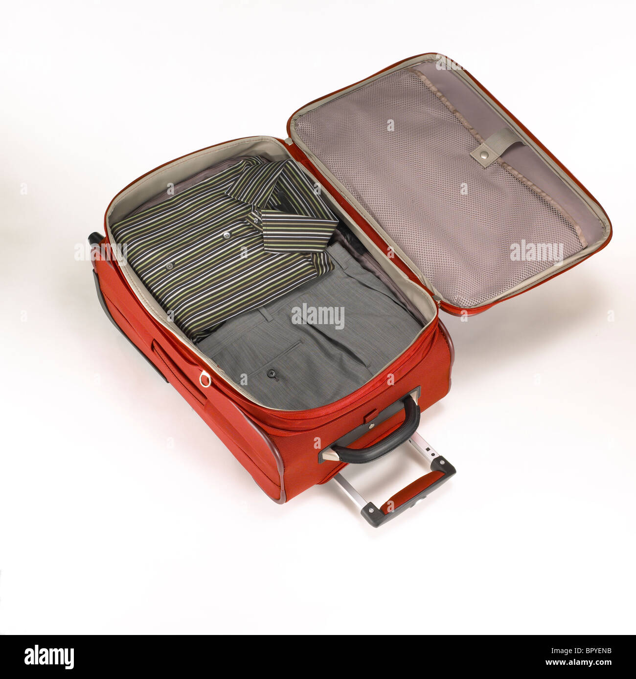 A red carry-on luggage with contents. - Stock Image