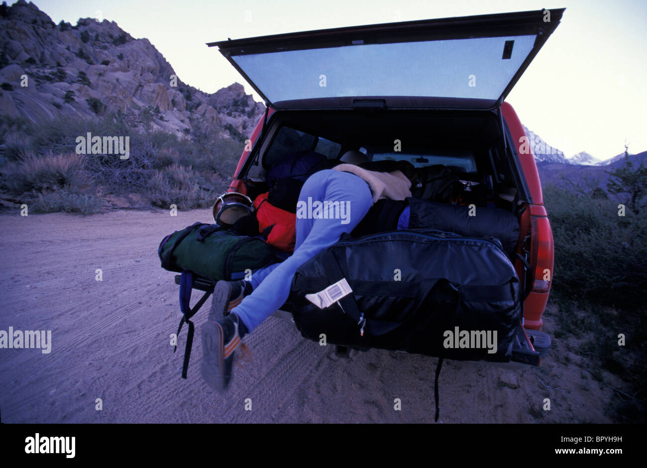 ff370c27 A woman searches for an item in her car, which is packed with duffel bags