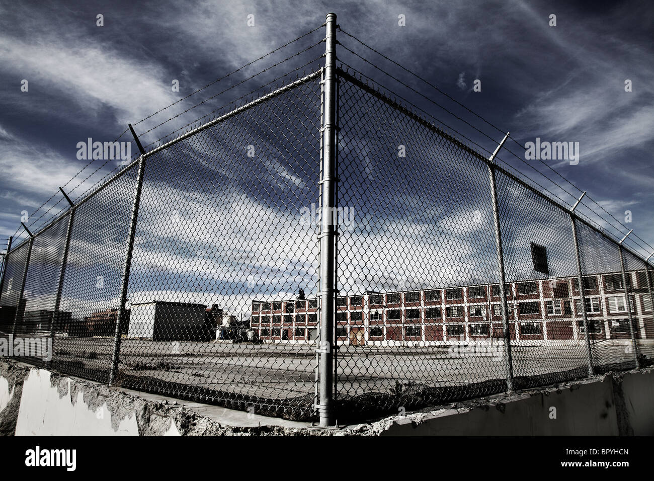 A fence in front of a factory building with a dramatic sky. - Stock Image
