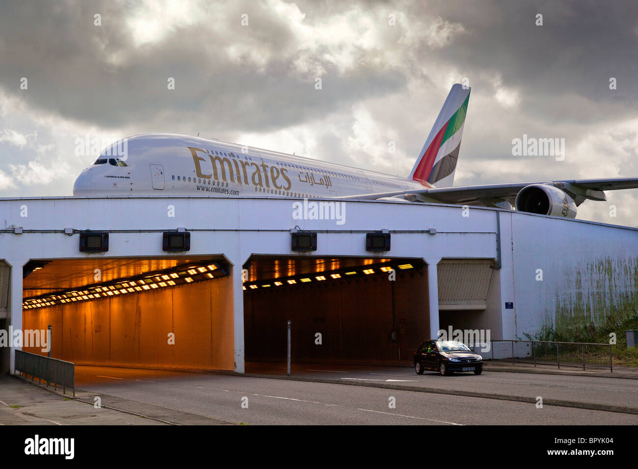 Emirates Airbus A380-800 arrives at Manchester airport, taxis across roadway inbound on the daily service EK017 - Stock Image