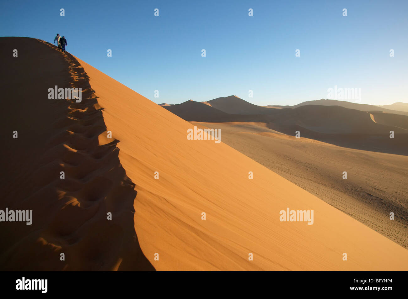 Travelers hike a dune ridge, Namibia - Stock Image