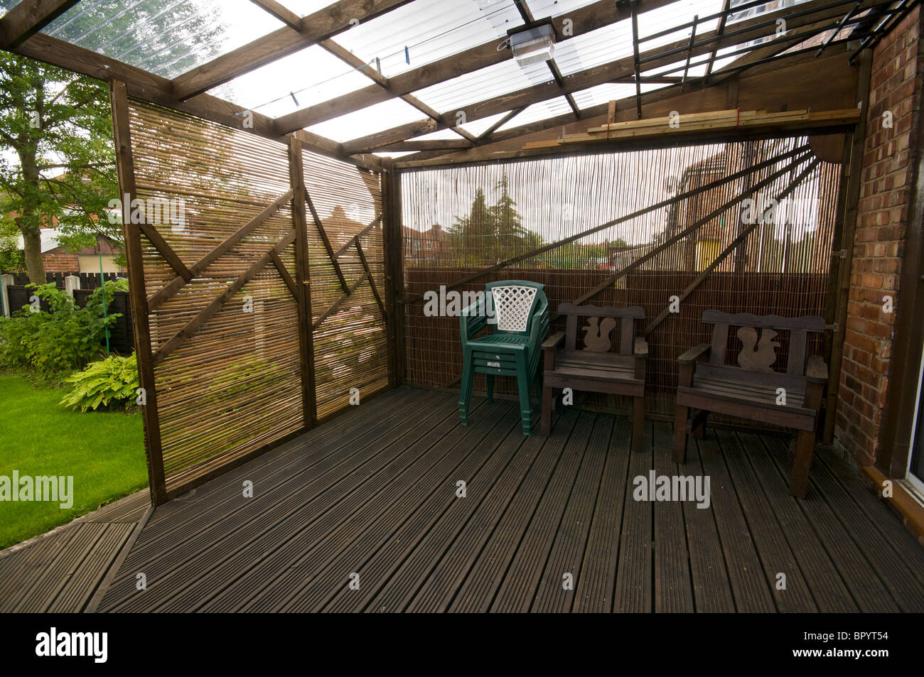 Elegant Home Built Patio Decking With Corrugated Plastic Roofing And Movable  Screening Panels In A Domestic Setting. Manchester, UK.