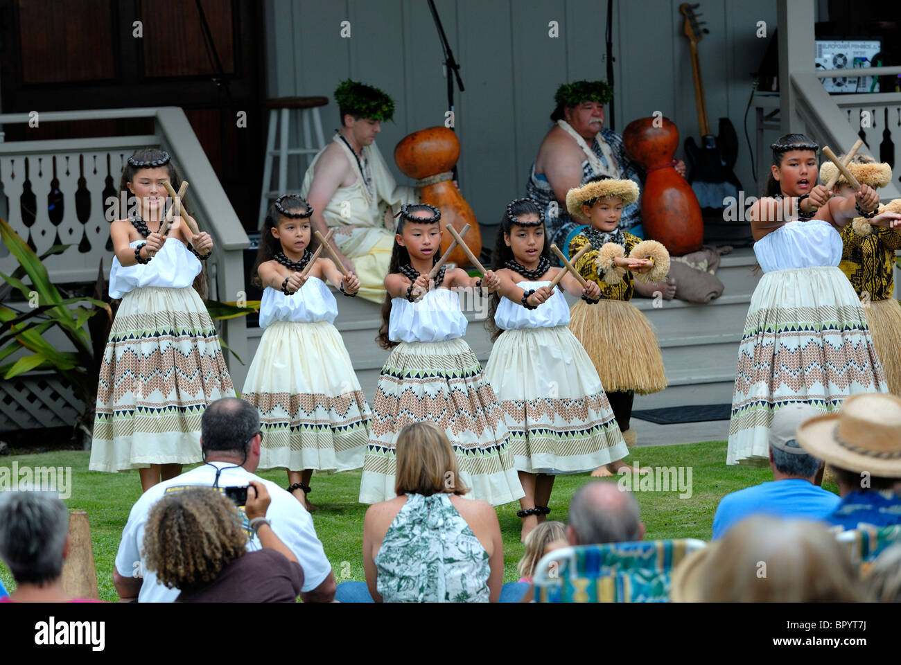 Children performing traditional Hawaiian music and dance at the Hulihe'e Palace, in honour of Hawaiian royalty. - Stock Image