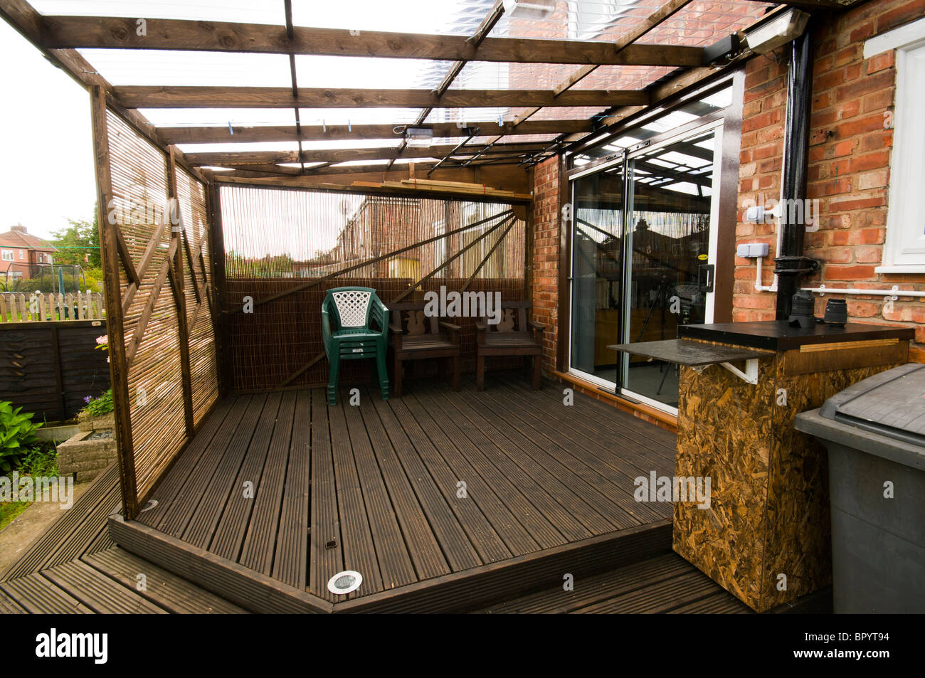 Great Home Built Patio Decking With Corrugated Plastic Roofing And Movable  Screening Panels In A Domestic Setting. Manchester, UK.