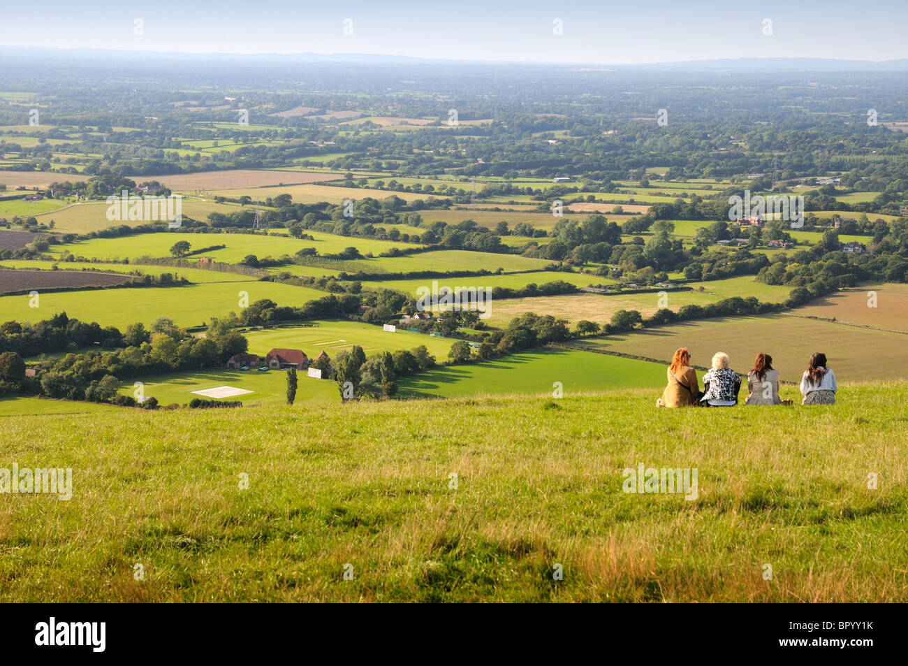 Four people sitting on hillside with South Downs National in background - Stock Image