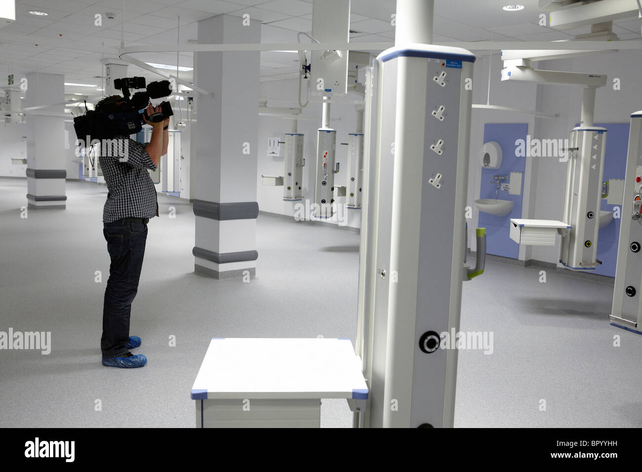 A television cameraman films inside a new hospital for TV news. - Stock Image